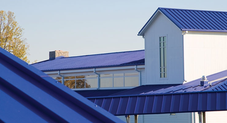 The Center features 16 buildings with unified white exteriors and metal roofing panels painted in Valspar's Fluropon coating in a vibrant Award Blue.