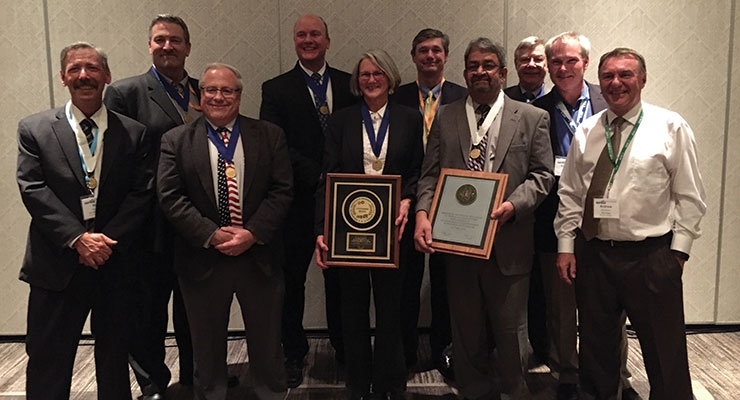 Dr. JoAnn Arceneaux, fifth from left and Dr. KumaR Menon, fourth from right, are congratulated by past NAPIM honorees, from left, Dan DeLegge, Pete Notti, Jerry Napiecek, Jon Graunke, Rich Bradley, Joe Cichon, Greg Webb and Andrew Matthews.