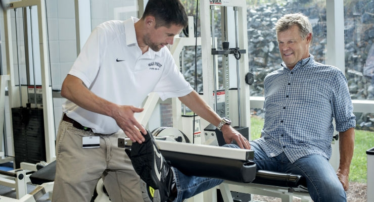 Physical therapist Bradley Fowler positions knee replacement patient Steven Jokinen on a piece of exercise equipment during a post-surgery rehabilitation session at Wake Forest Baptist Medical Center. (Credit: Wake Forest Baptist Medical Center/Cameron Dennis)