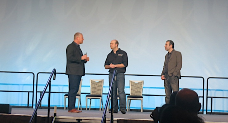 Keith Wilmot (L) discusses a chance Dscoop opportunity with the founders of DigiWrap.