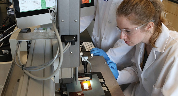 UMass Lowell graduate students Kyle Homan, left, and Elicia Harper work in one of the labs at the UMass Lowell's Mark and Elisia Saab Emerging Technologies and Innovation Center. The $80 million facility is home to the Printed Electronics Research Collaborative. (Photo credit: Joson Images for UMass Lowell)