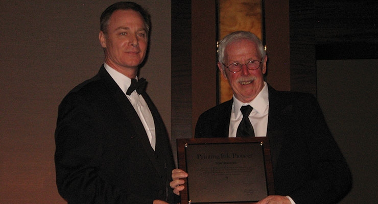 Tom Rogers, right, retired president and CEO of Apollo Colors, accepts NAPIM's Pioneer Award from NAPIM president Pat Carlisle.