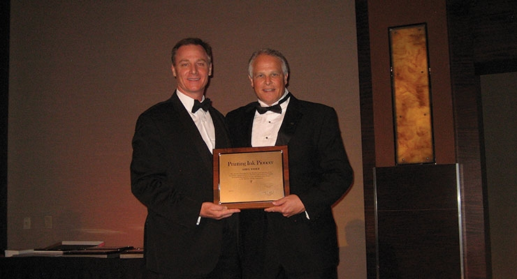 Greg Yoder, right, of Flint Group accepts NAPIM's Pioneer Award from NAPIM president Pat Carlisle.