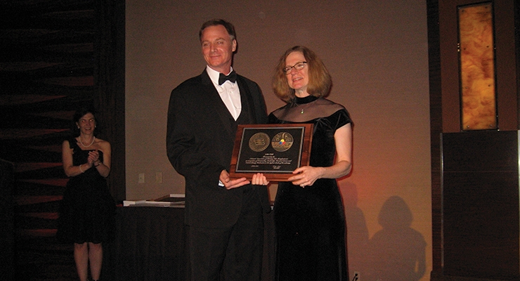 Lisa Fine, right, of Joules Angstrom U.V. Printing Inks, accepts NAPIM's Pioneer Award from NAPIM president Pat Carlisle.