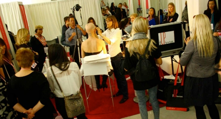 A makeup demo on the show floor at MakeUp in NewYork
