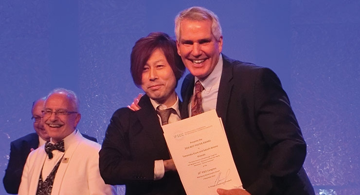 Shiseido's Tomonobu Ezure accepts the poster award from Greg Hillebrand.