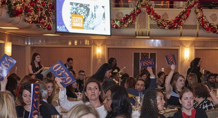 3. Auction Excitement: Beauty execs bid on prizes during the live auction at CEW's annual Beauty of Giving Luncheon 2016. Photo by JF Productions.
