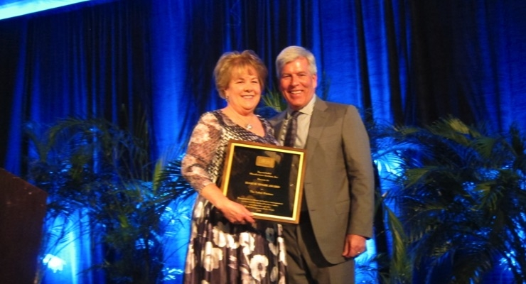 Lori Campbell of The Label Printers accepts the Eugene Singer award from TLMI chairman Craig Moreland