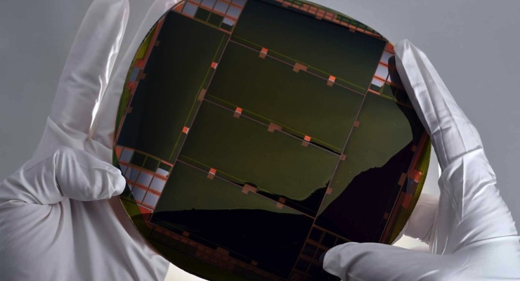 Two hands holding the IMM solar cellA 6-inch MicroLink Devices high-efficiency, lightweight and flexible ELO IMM solar cell wafer. (Photo courtesy of MicroLink Devices)