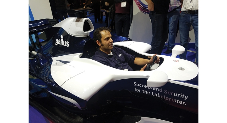 L&NW editor Steve Katz takes a quick break during Labelexpo to check out the Formula One simulator at the Gallus booth.