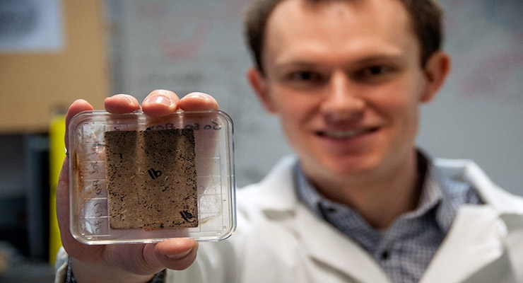 UBC researcher Bryn Crawford holds a sample sheet made with flax bio-waste. The black spots on the sheet indicate mold growth.