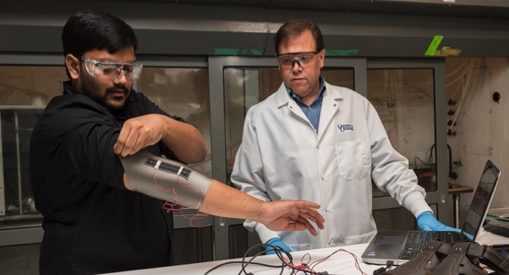 Sagar Doshi, left, and Erik Thostenson test an elbow sleeve outfitted with one of their novel sensors. (Photo by Kathy F. Atkinson)