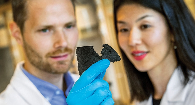 Petter Tammela from Ångström Laboratory and Shoko Yamada from BillerudKorsnäs study the material that becomes the paper battery. (Photo: BillerudKorsnäs)
