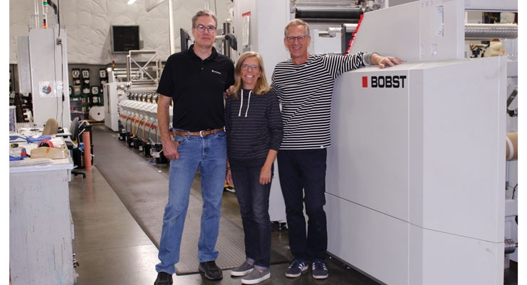 With one of the company's two Bobst presses, from left, Paul Polewko, production manager; Sally Revere, co-owner; Mark Revere, co-owner.