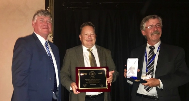 Mark Hill of INX International Ink Company, center, receives the NAPIM Technical Achievement Award from NAPIM president Jim Leitch, left, and NPIRI president Dan Delegge during the 2018 NPIRI Technical Conference.