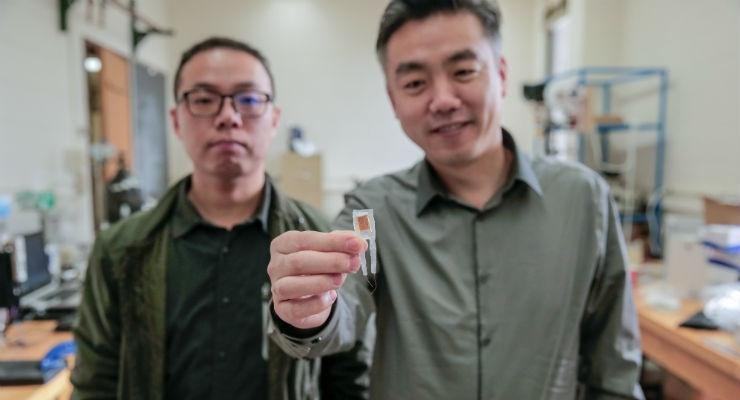 Graduate student Guang Yao (left) and Xudong Wang (right) hold a small implantable device that helped rats lose 40 percent of their body weights. Image courtesy of Sam Million-Weaver.