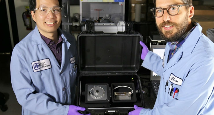 Sandia National Laboratories chemist Chung-Yan Koh, left, and former Sandia bioengineer Chris Phaneuf hold the newly updated SpinDx diagnostic device. Image courtesy of Jules Bernstein.