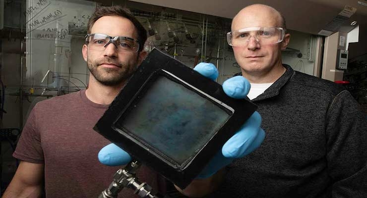 NREL Researcher Lance Wheeler (left) holds a sample of the SwitchGlaze technology alongside Robert Tenent, the laboratory