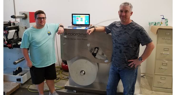 Joshua Schmitt (L), CSR/ Digital Specialist, and Darrin Schmitt, President, stand alongside ALT's Colordyne 2600 Series Mini Press.