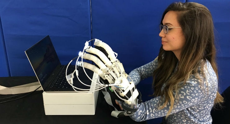 Alexandra Lindsay, a junior scientist at UTARI, displays the rehab glove. Image courtesy of UT Arlington.