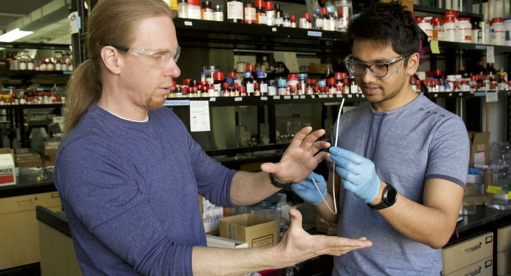 David Lynn, left, a professor of chemical and biological engineering at the University of Wisconsin–Madison, and graduate student Harshit Agarwal discuss the super-slippery coatings they are developing to reduce bacterial growth on implanted medical devices, such as catheters. Image courtesy of David Tenenbaum.