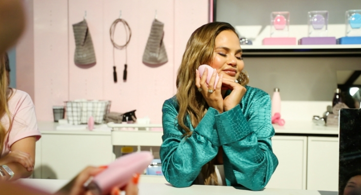 Chrissy Teigen massages her face with the LUNA 3 at the FOREO booth at POPSUGAR Play/Ground. (Photo: Thomas Crane)